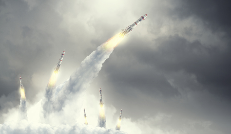 Military missiles flying high in blue sky