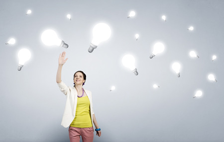 reaching hand: Businesswoman reaching hand to touch glass glowing light bulb