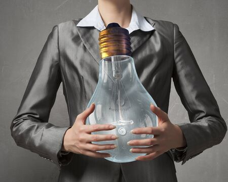 holding close: Close view of businesswoman holding in hands glass glowing bulb Stock Photo