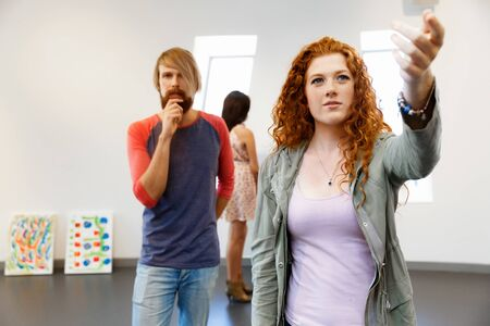 baby boomer: Young artists in gallery hanging together painting on walls Stock Photo
