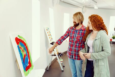 Young caucasian couple standing in a gallery and contemplating abstract artwork Stock Photo