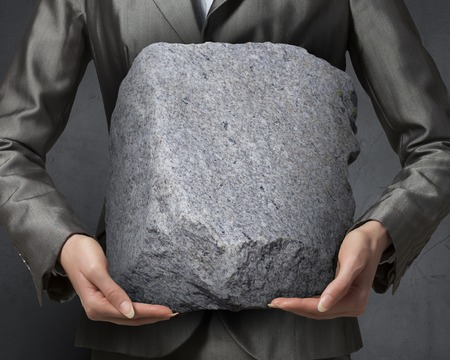 overpowering: Close view of businesswoman holding big heavy stone