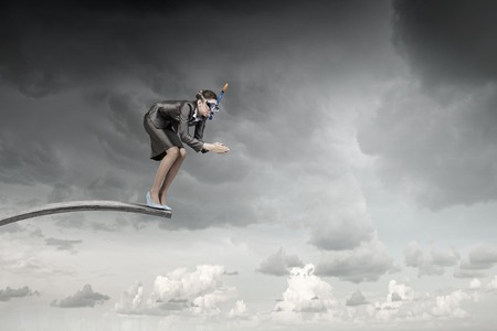 Businesswoman in suit and mask jumping from springboard
