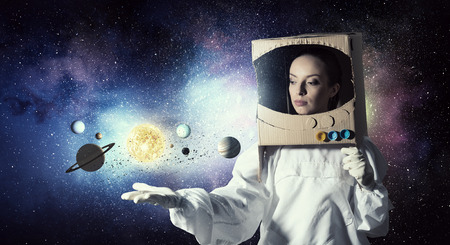 faculty: Young woman with carton box on head imagine she is astronaut Stock Photo