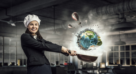 Pretty businesswoman in suit and cook hat with pan in hand. Elements of this image are furnished by NASA