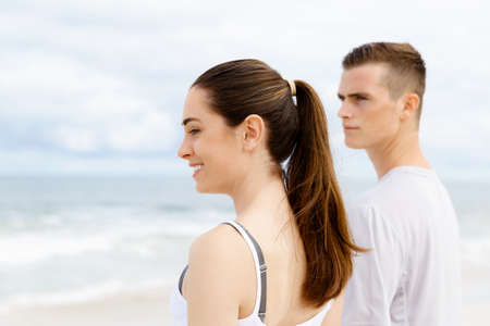 sports wear: Young couple looking thoughtful while standing next to each other on beach in sports wear