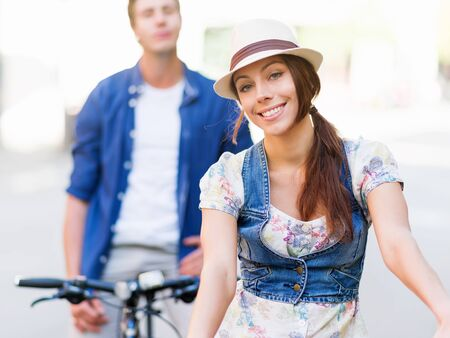 Beautiful young woman riding on bike in city Stock Photo