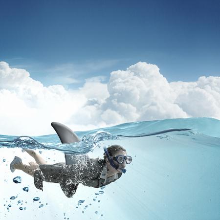 flipper: Young businesswoman with shark flipper swiming under water