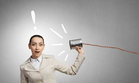 hear business call: Young businesswoman using tin can and string as communication tool