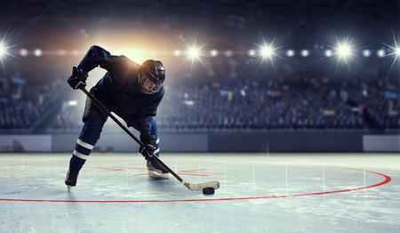 スポット ライトでアイスリンクにブルーの制服でホッケー選手