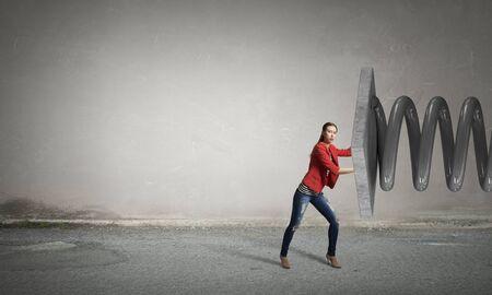 resisting: Young woman in red jacket resisting big metal spring Stock Photo