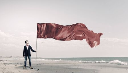 windy energy: Young student guy with color blank waving flag Stock Photo