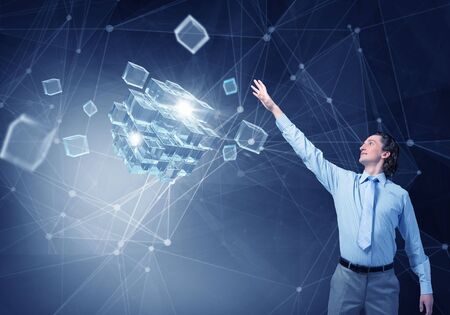 reaching: Businessman reaching hand to touch 3D rendering cube figure