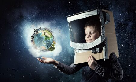 become: Cute kid boy with carton helmet on head dreaming to become astronaut.