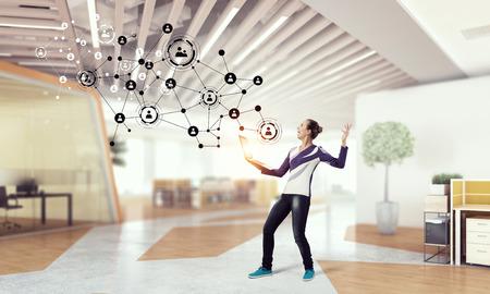 administrador de empresas: Mujer joven en ocasional con la computadora portátil que presenta concepto de red social,