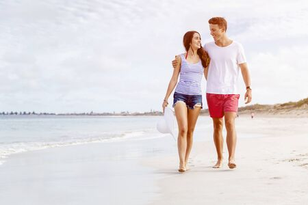 Romantic young couple on the beach walking along the shore