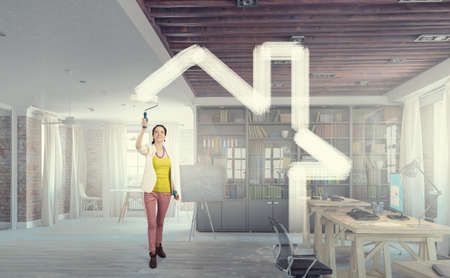 Woman with a painting roller or brush in renovate interior