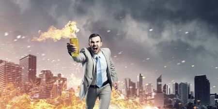 sabotage: Aggressive businessman in suit throwing burning molotov cocktail