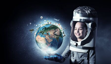 become: Cute kid girl with carton helmet on head dreaming to become astronaut. Elements of this image are furnished by NASA