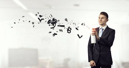 Businessman spraying his business symbols from aerosol can Stock Photo