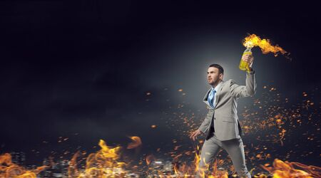 anarchist: Aggressive businessman in suit throwing burning molotov cocktail