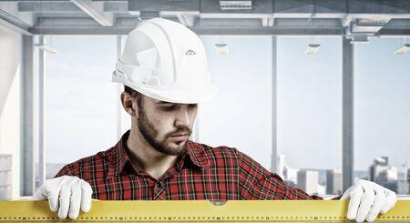 Engineer man in helmet indoor using level. Mixed media Standard-Bild