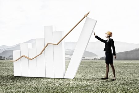 woman engineer: Young woman engineer and growing graph bars