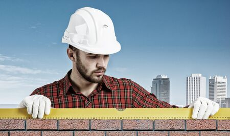 Bricklayer using level to check new red brick wall outdoor