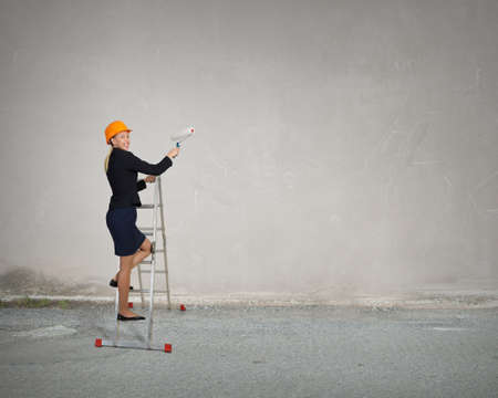 climbing ladder: Attractive engineer woman with paint roll climbing ladder