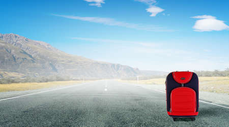 Travel concept with red suitcase on road
