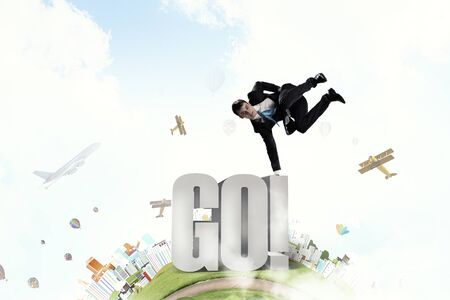 lean: Active businessman making handstand on word go Stock Photo