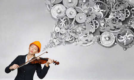 young engineer: Young engineer woman with closed eyes playing violin instrument Stock Photo