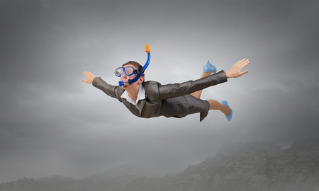 Young businesswoman in suit and diving mask flying in sky