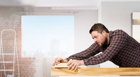 Carpenter in interior working with jointer tool. Mixed media Stock Photo