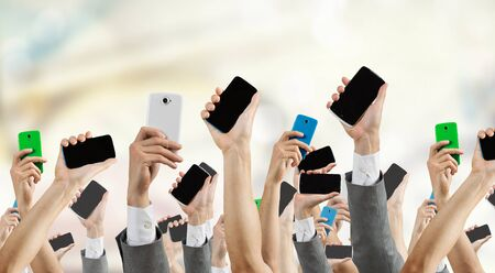 electronic voting: Group of people with hands up showing mobile phones
