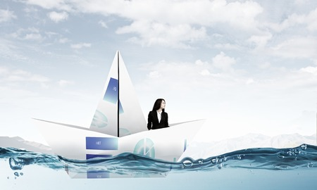 Businesswoman floating in boat made of paper