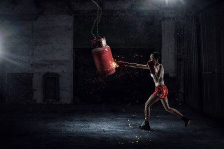 desolate: Young pretty woman boxing in desolate building. Mixed media
