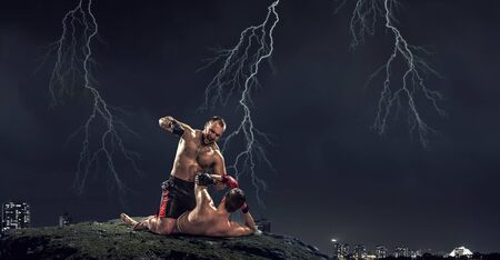 Two strong fighters outdoor demonstrating ultimate fighting