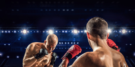 Two professional boxers fighting on arena in spotlights