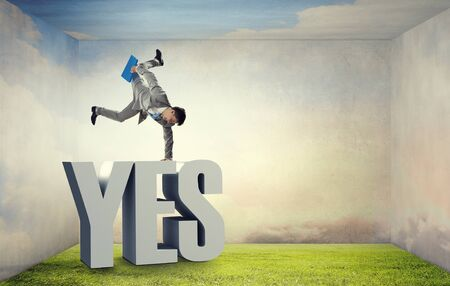handstand: Active businessman making handstand on word yes