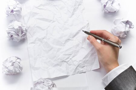 crumpled sheet: Hand of businesswoman writing on blank crumpled sheet of paper