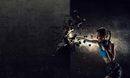 boxeador de la mujer joven que rompe la pared de hormigón con patada Foto de archivo