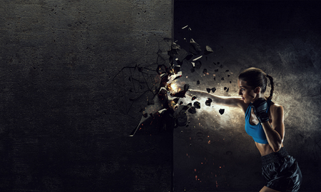 Young boxer woman breaking concrete wall with kick Reklamní fotografie
