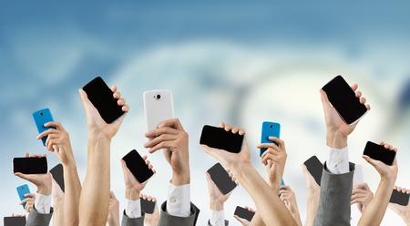 Grupo de personas con las manos arriba que muestra los teléfonos móviles Foto de archivo - 61120388