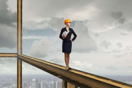 balk: Young woman architect in hardhat holding project in hand Stock Photo