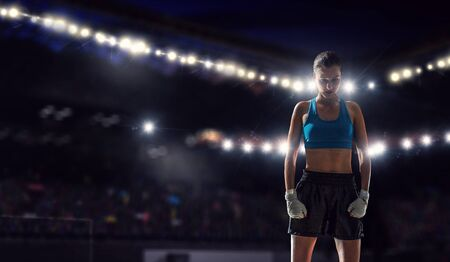 Young pretty boxer woman standing in lights of sport arena