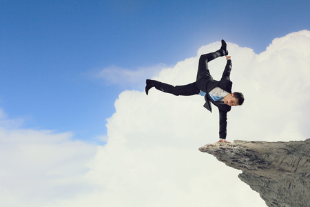 handstand: Active businessman making handstand on rock edge Stock Photo