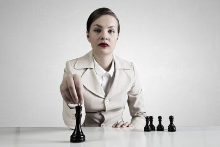 pensamiento estrategico: Empresaria bastante joven sentado en la mesa y jugar al ajedrez