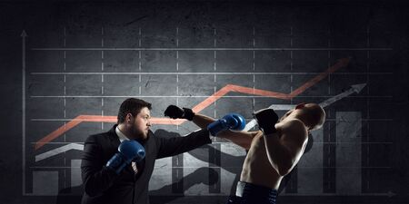 financial market: Young businessman in boxing gloves knocking opponent and infographs at background