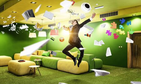 Funny jumping businessman in modern 3D rendering interior. Mixed media Stock Photo